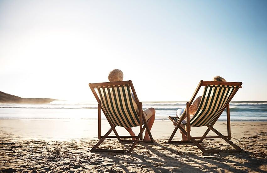 זוג יושב על כסאות נח בשפת הים מול השקיעה