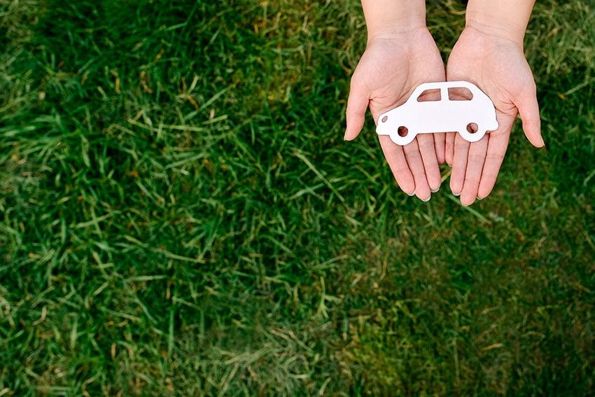 מכונית צעצוע לבנה על גבי כפות ידיים