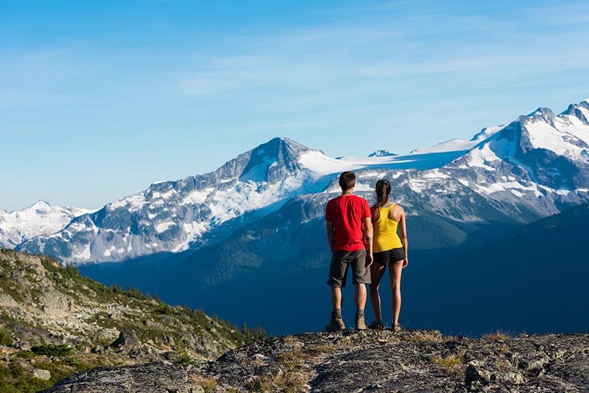 זוג עומד על הר וצופה על הנוף
