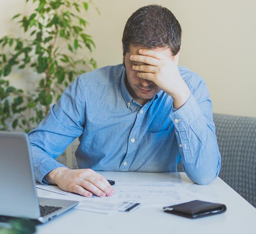 איש בחולצה מכופתרת מוטרד רוכן מעל דפי בנק