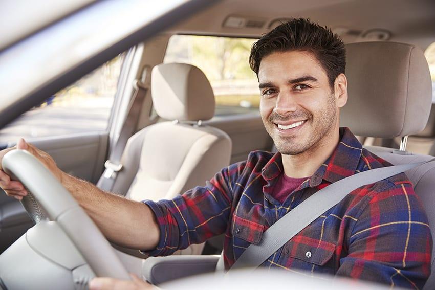 גבר יושב ברכב חגור בחגורת בטיחות
