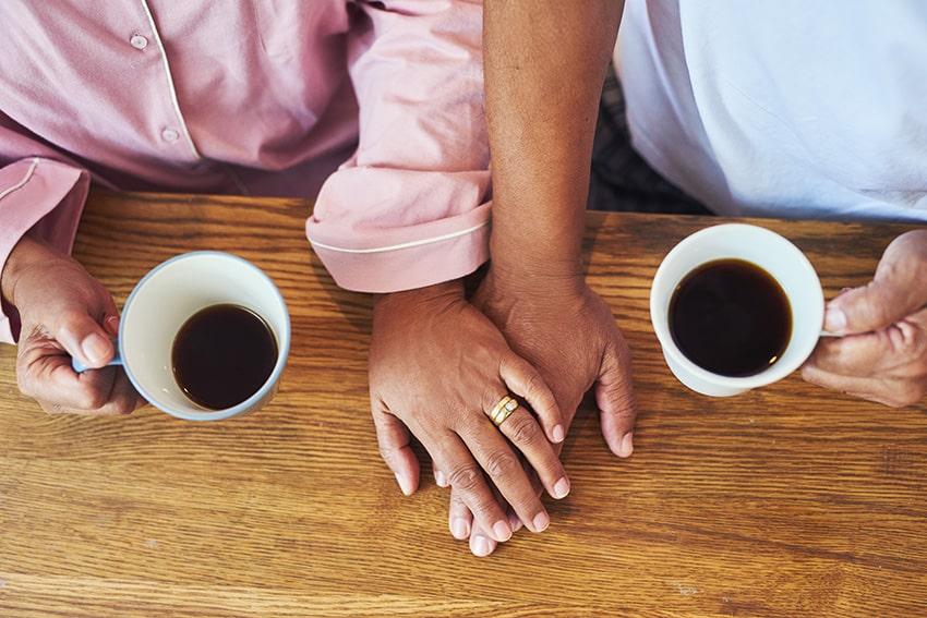 זוג עומד ליד שולחן עם כוסות קפה חצי ריקות