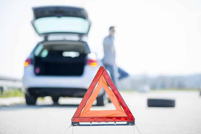 תמרור אזהרה משולש אדום על כביש לפני רכב עם תא מטען פתוח