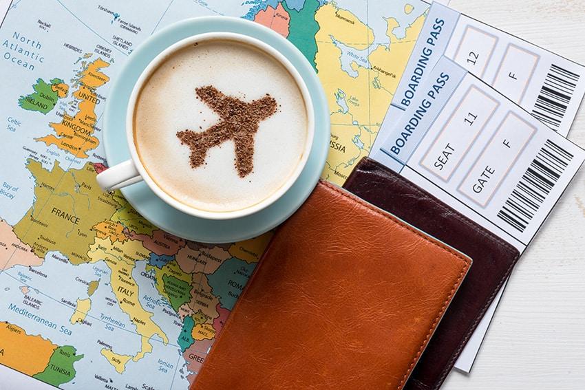 מטוס מצוייר על כוס קפה שנמצא מעל מפת העולם ליד מסמכי נסיעה