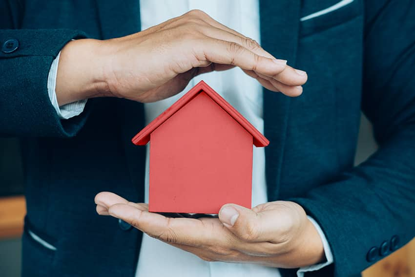 סוכן ביטוח מגונן בידיו על מודל של בית אדום