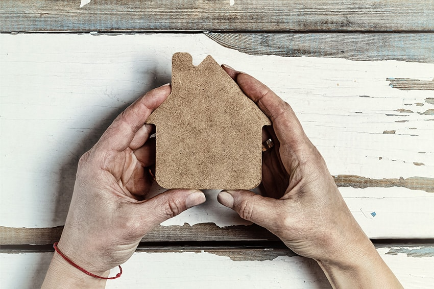 ידיים מחזיקות בית מקרטון