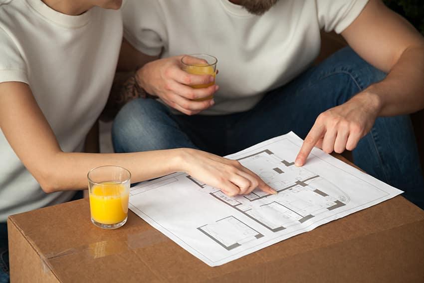 זוג בחולצות לבנות שותה מיץ תפוזים ומסתכל בתרשים דירה