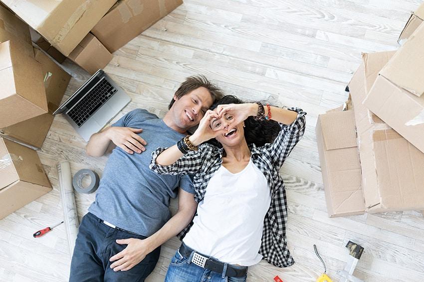 זוג צעיר מאושר שוכב על רצפת פרקט ומסביבו ארגזי מעבר דירה