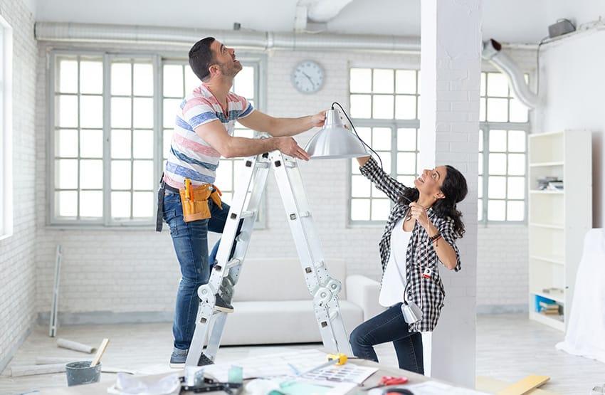 כבר מטפס על סולם ומחזיק עם אשה מנורה בבית בשיפוץ